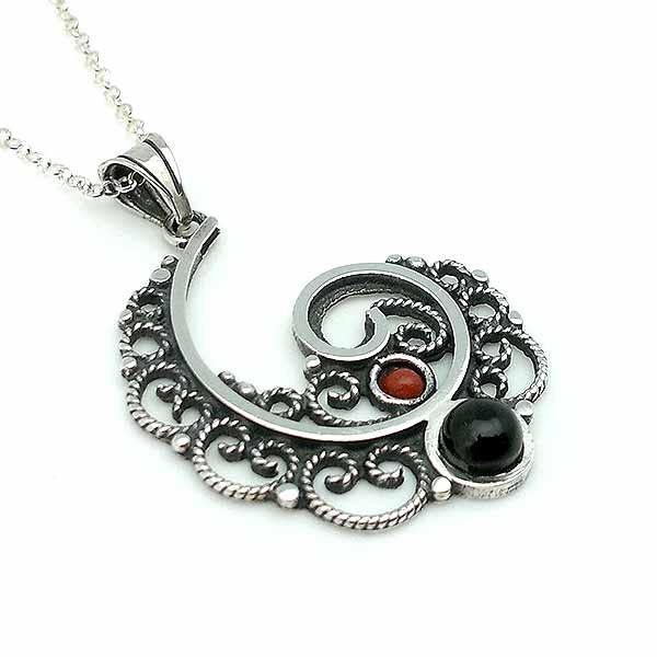 Colgante, hecho con forma de spiral, en plata de ley, azabache y coral.