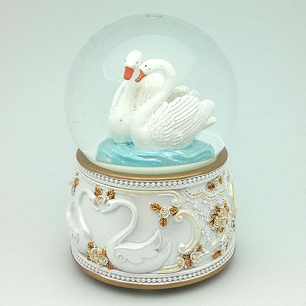 Snowball, with a pair of swans on a lake.