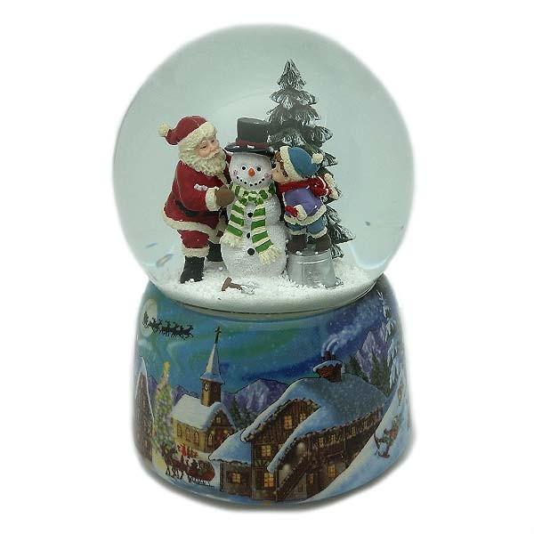 Bola de nieve en la que podemos ver a papá Noel y a un niño haciendo un muñeco de nieve.