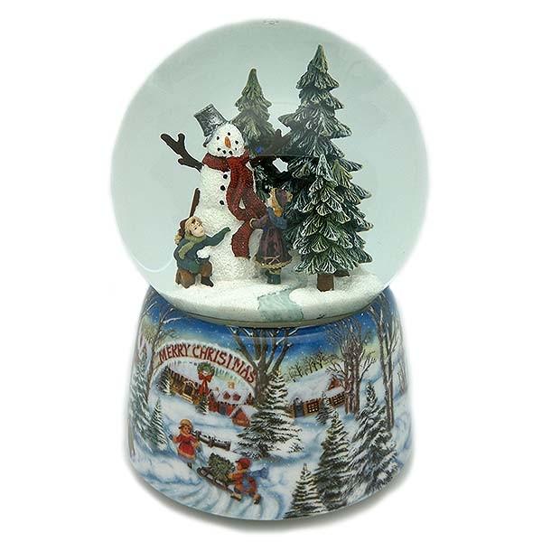 Bola de nieve navideña, en la que vemos a un niño y una niña construyendo un muñeco de nieve.