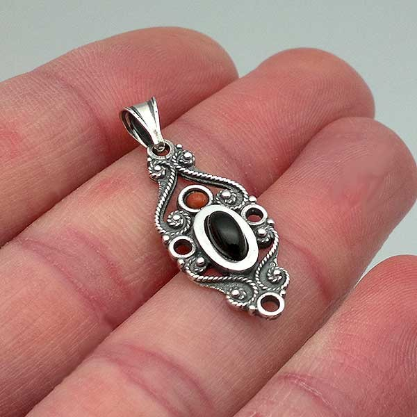 Classic pendant, made of sterling silver, jet and coral.
