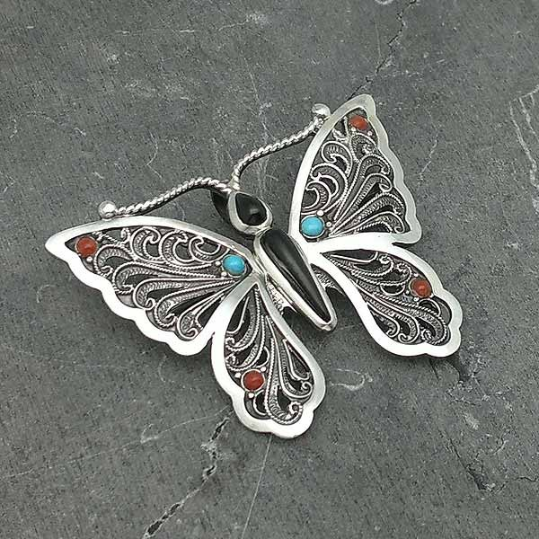 Brooch in the shape of a butterfly, handcrafted in sterling silver and natural stones.