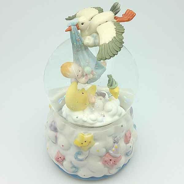 Bola de nieve bebé y cigueña